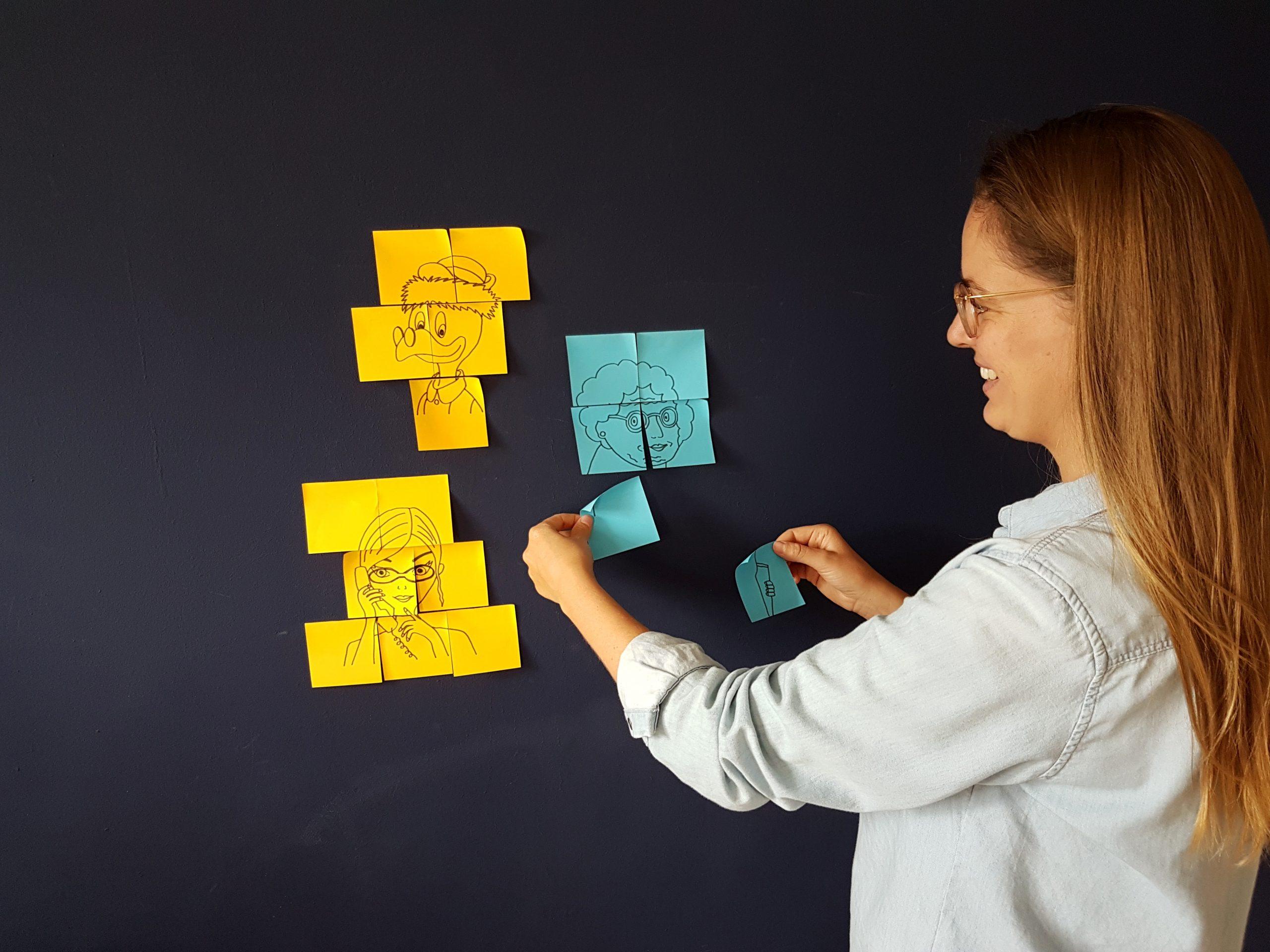 Ontwerper Daphne brainstormt alleen met gekleurde post-its op een paarse wand.