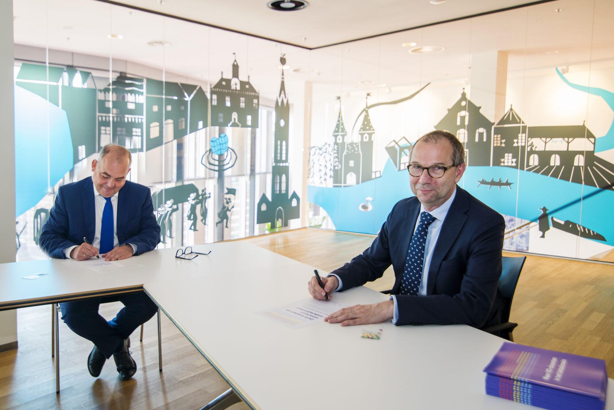 Initiatiefnemer Rob Mudde (TU Delft) ondertekent de samenwerking met wethouder Lennart Harpe (Gemeente Delft).